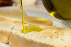 Dolewania oliwa z oliwek na grzance Fotografia Royalty Free