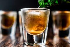 Dolewania whisky strzały z lodem na ciemnej drewnianej powierzchni fotografia stock