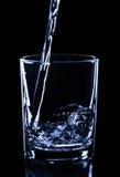 Dolewanie błękitne wody na szkle odizolowywającym na czerni, zamyka up, pojęcie Obraz Royalty Free