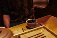 Dolewanie ciemna pu herbata od purpurowego glinianego słoju w małą smaczną filiżankę obrazy stock