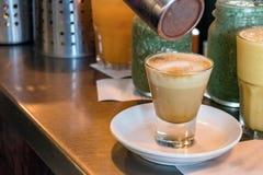 Dolewanie cynamon na cappuccino kawie w przejrzystym szkle przy sklepu z kawą kontuarem zdjęcia stock