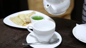 Dolewanie herbata w białą filiżankę na stole od porcelana czajnika galareta i blin na tle zbiory