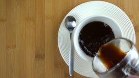 Dolewanie kawa w białą filiżankę zbiory