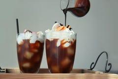 Dolewanie nakrywa na deserze z zimną parzenie kawą obrazy royalty free