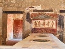 Ruins of Pompeii, ancient Roman city. Pompei, Campania. Italy. Dolias and fresco detai, of archaeological remains of Thermopolium of Vetutius Placidus, at Ruins stock image