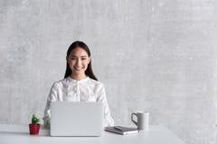 Dolkomische het glimlachen vrouw plaatsbepaling in bureau stock foto's
