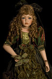 Doll. Young doll in green dress and curls on the head on dark background Royalty Free Stock Images