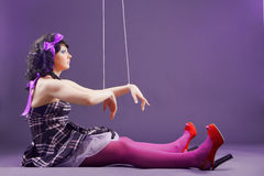 Doll. Fashion model stylized as marionette doll sitting on violet studio background Royalty Free Stock Photos