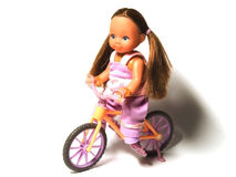 Doll bicycle. Doll of a little girl on a bicycle Stock Photography