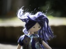Doll with blue hair blowing in the wind royalty free stock image