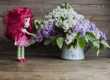 Doll with a bouquet. Of lilacs on a wooden background stock image