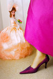 Doll bride. In the pink dress and wooman leg Royalty Free Stock Photos