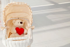 Doll buggy vintage with teddy bear and red heart royalty free stock image