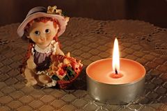 Doll and candle Stock Images