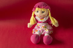 Doll. A children toy doll on red background Royalty Free Stock Image