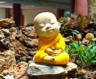 Doll clay monk in ornamental garden Stock Photos