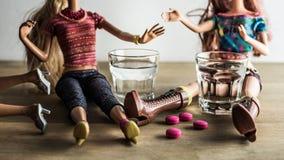 Doll die met schoten van wodka en roze pillen partying stock fotografie