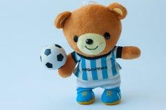 Doll draagt spelvoetbal Stock Afbeeldingen