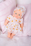Doll in a dress on a pink pillow Royalty Free Stock Photo