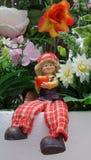 Doll in flower garden Stock Photos
