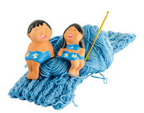Doll on fragment blue knitting cloth Royalty Free Stock Photos