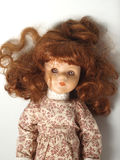 Doll. Ginger haired doll in printed dress laying on white background Royalty Free Stock Photos