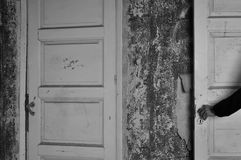 Doll hand haunted house door. Arm with doll hand on the door of a haunted house. Black and white royalty free stock images