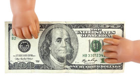 Doll Hands Grasping Cash. Baby doll hands grasping one hundred dollars in cash money Royalty Free Stock Images