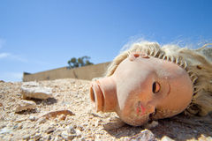 Doll head lying on the ground. Doll head with closed eyes lying on the ground with a blue sky in the background Royalty Free Stock Photos