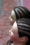 Doll heads. A closeup profile view of two doll heads with short braided hair Stock Photo