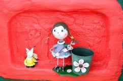 Doll in het tuindecor op rode achtergrond Royalty-vrije Stock Foto's