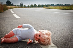 Doll leave on a highway lane Stock Photos