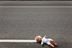 Doll leave on a highway lane Royalty Free Stock Image
