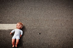 Doll leave on a highway lane Royalty Free Stock Images