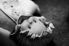 Doll left behind. Close-up of doll left behind laying on the floor unattended. High contrast grainy black and white picture with narrow depth of field and copy Royalty Free Stock Image