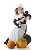 Doll-Loving Pilgrim. An elemantary-aged Pilgrim sitting on an old log loving on her Pilgrim doll, two pumpkins in the foreground.  On a white background Stock Image