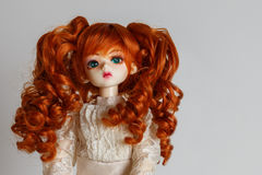 A doll with lush red hair in an antique dress.  Royalty Free Stock Photos