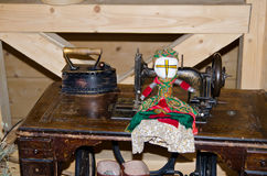 Doll motanka on the background of an old sewing machine and iron. The ancient craft. Motanka - Ukrainian folk doll protecting the Stock Image