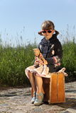 Doll Mummy. Little girl with an antique doll sitting on a suitcase at the street Royalty Free Stock Photo