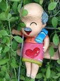 Doll op schommelings borad pop Stock Afbeeldingen