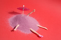 Doll and pink sand. Arm and leg`s doll emerging from a pile of pink sand as if it were hiding. Minimal funny and quirky design still life photography Stock Photography
