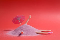 Doll and pink sand. Arm and leg`s doll emerging from a pile of pink sand as if it were hiding. Minimal funny and quirky design still life photography Royalty Free Stock Photos