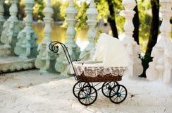 Doll& x27; s摇篮车 葡萄酒在台阶安置的玩偶婴儿推车对一个美丽的湖 减速火箭的推车玩偶由藤条和白色鞋带制成 免版税库存照片