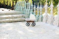 Doll& x27; s摇篮车 葡萄酒在台阶安置的玩偶婴儿推车对一个美丽的湖 减速火箭的推车玩偶由藤条和白色鞋带制成 免版税库存图片