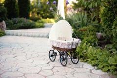 Doll& x27; s-pram Tappningdockasittvagn som förläggas på stengångbanan, gränd i en härlig trädgård royaltyfria bilder