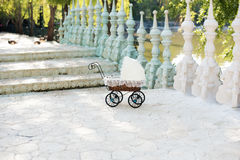 Doll's pram. Vintage doll stroller placed on the stairs to a beautiful lake. Retro cart dolls made of rattan and white lace. royalty free stock images