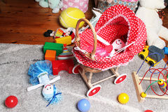 Doll's trolley in child's room. And other toys on the floor Royalty Free Stock Image