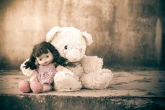 Doll sad with teddy bear. Vintage tone Royalty Free Stock Image
