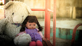 Doll sad with teddy bear. Vintage tone Stock Images