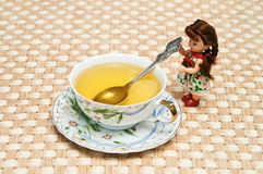 Doll serving tea. Small beautiful doll serving green tea Royalty Free Stock Image